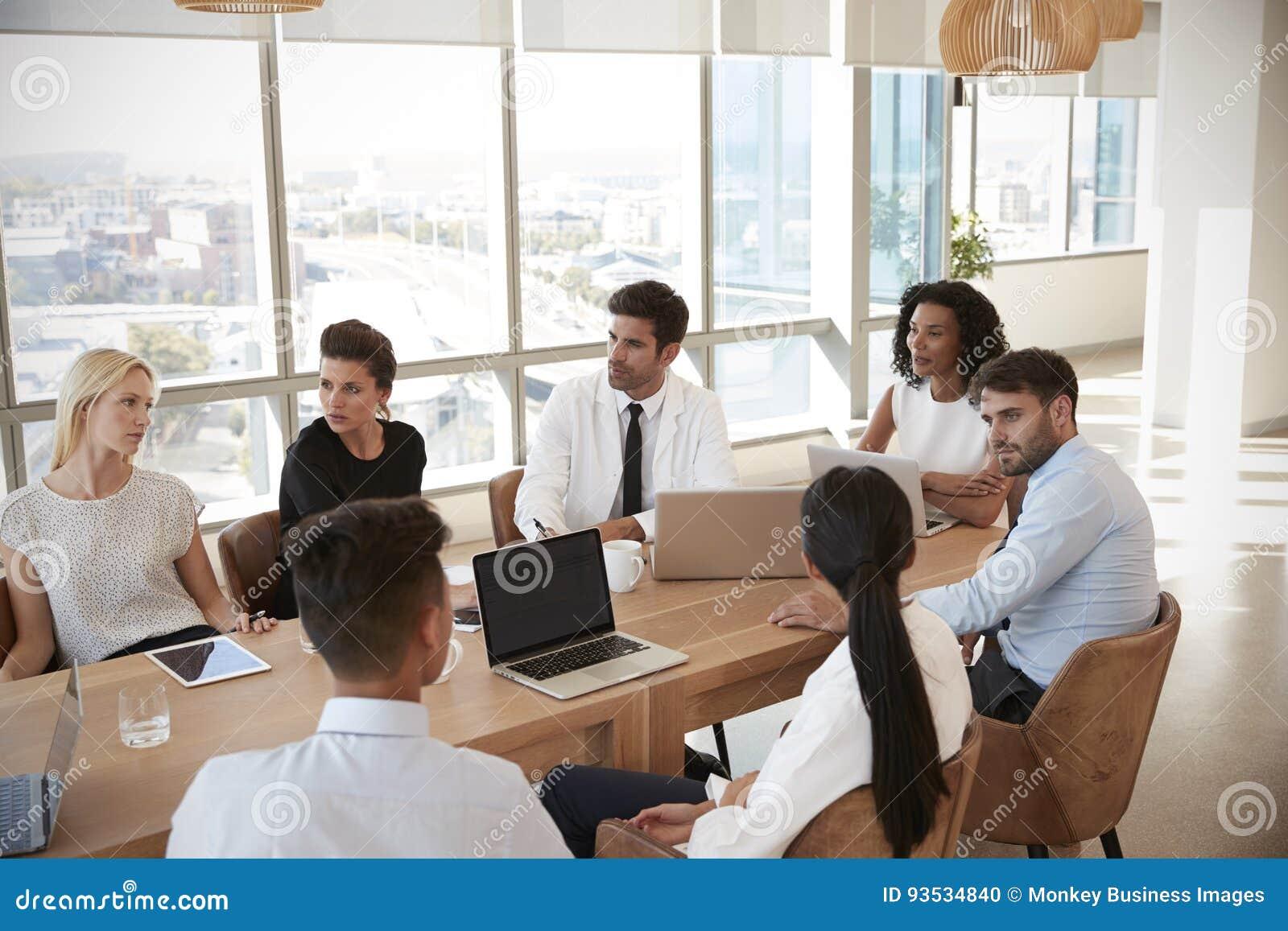 Grupp av mötet för medicinsk personal runt om tabellen i sjukhus