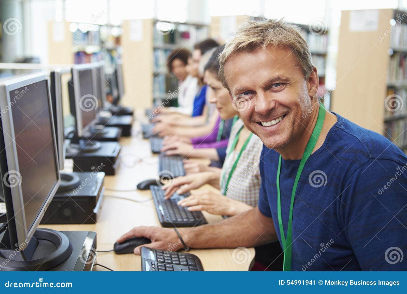 Grupp av mogna studenter som arbetar på datorer