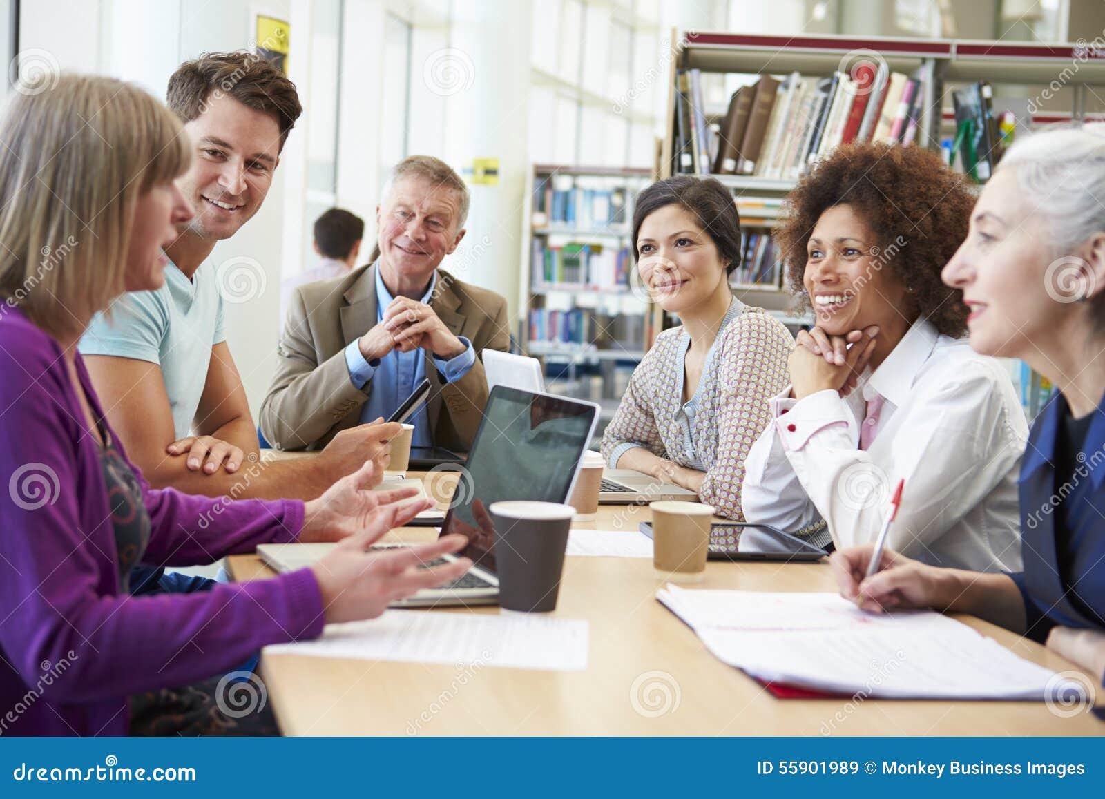 Grupp av mogna studenter som samarbetar på projekt i arkiv