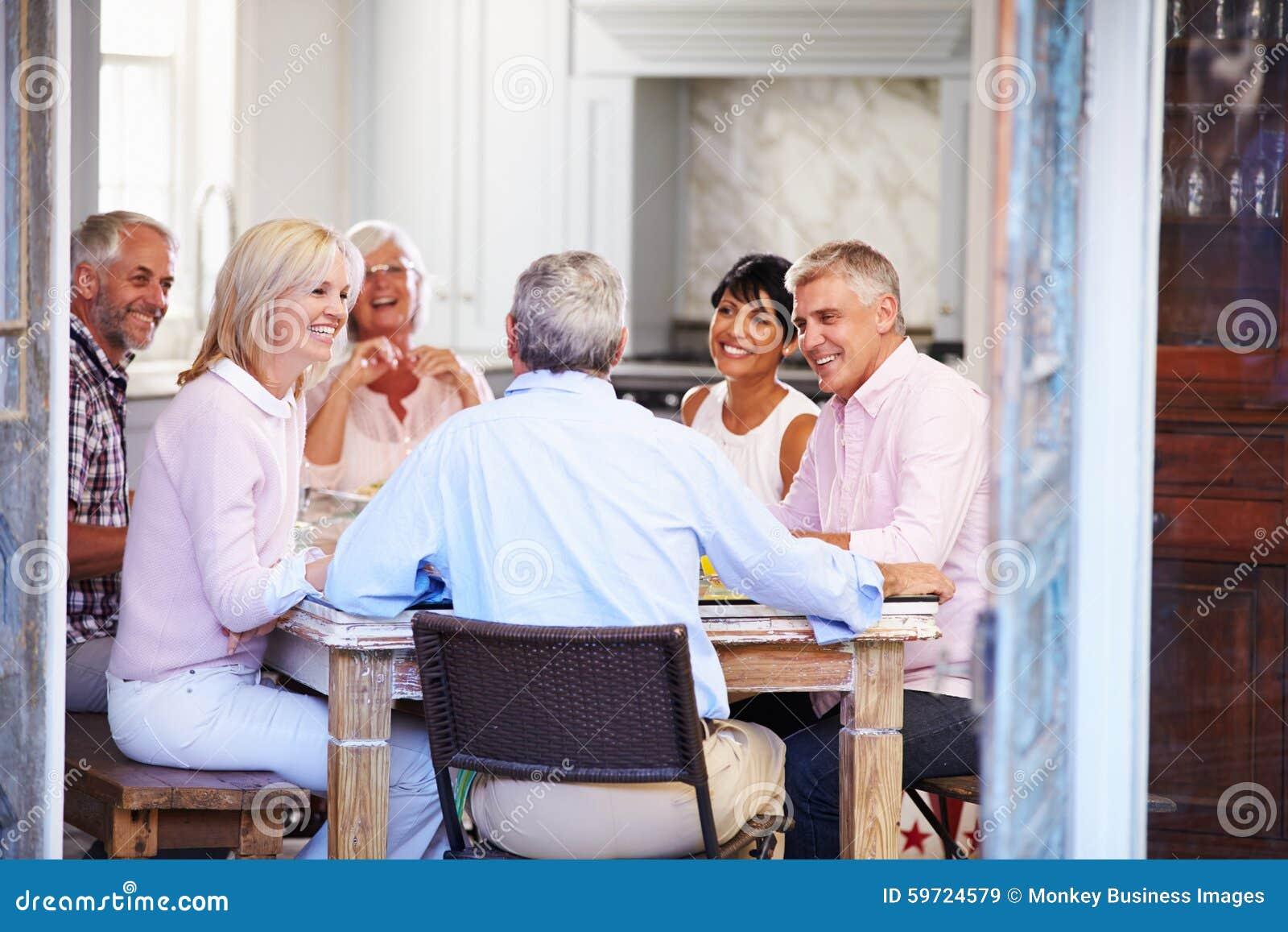 Grupp av mogna vänner som hemma tycker om mål tillsammans