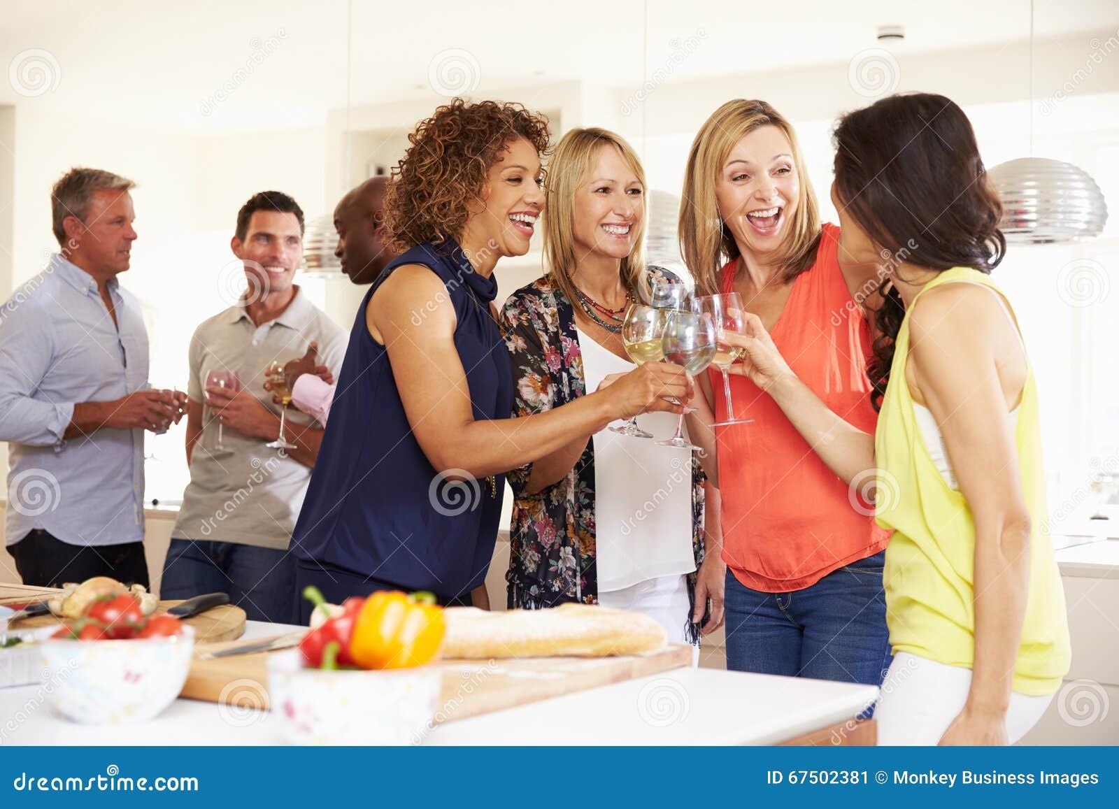 Grupp av mogna vänner som hemma tycker om matställepartiet