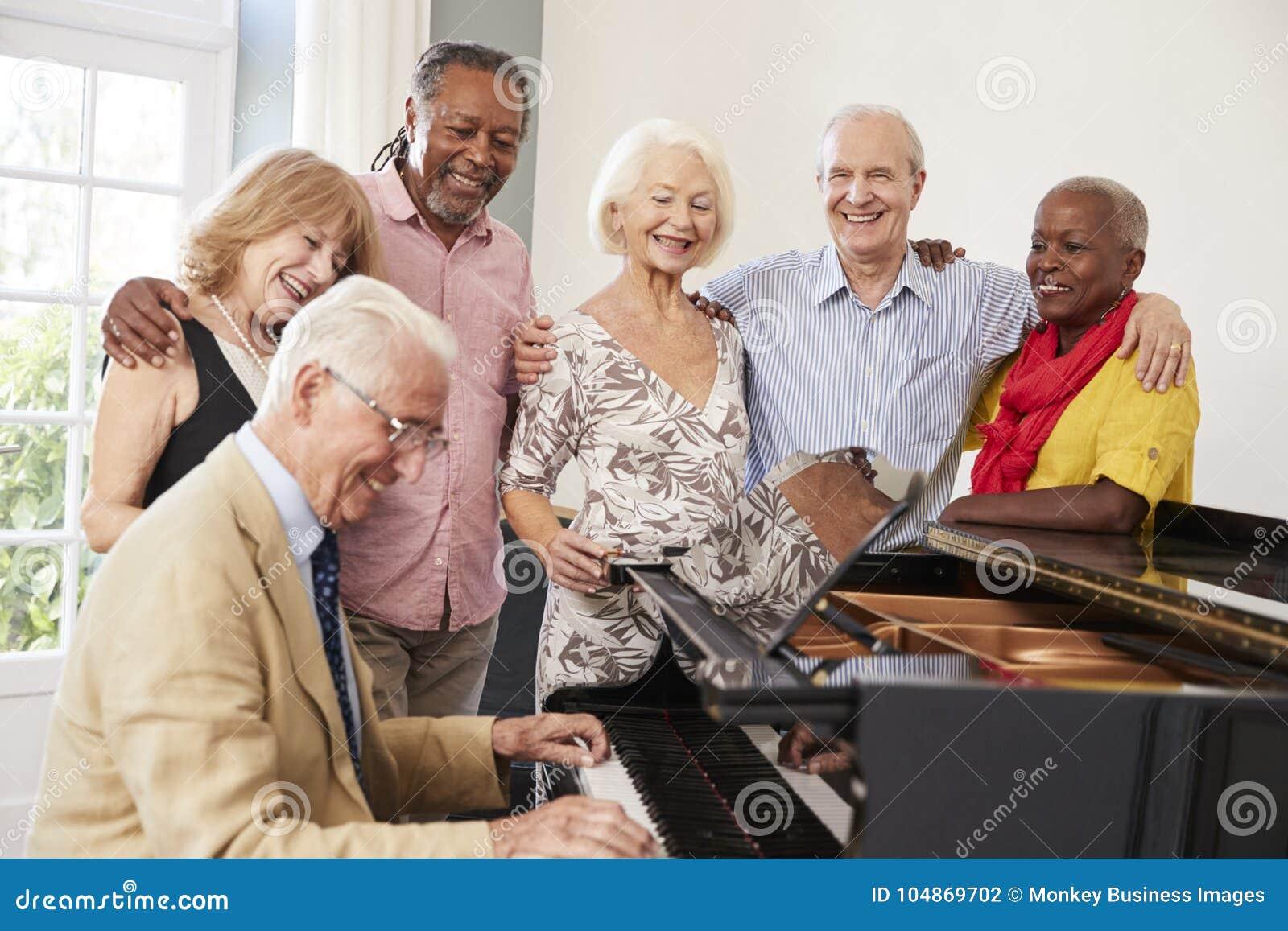Grupp av pensionärer som står vid pianot och tillsammans sjunger