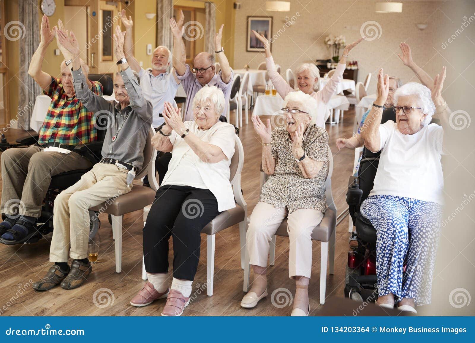 Grupp av pensionärer som tycker om konditiongrupp i avgånghem