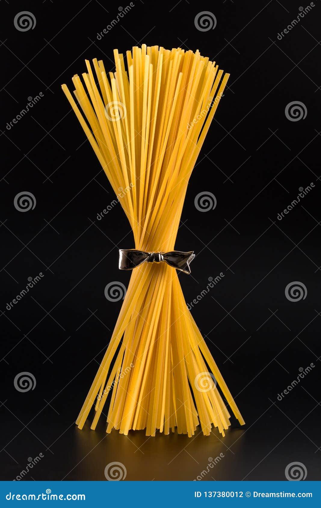 Grupp av spagetti som står som är upprätt på en ljus svart bakgrund vertikalt