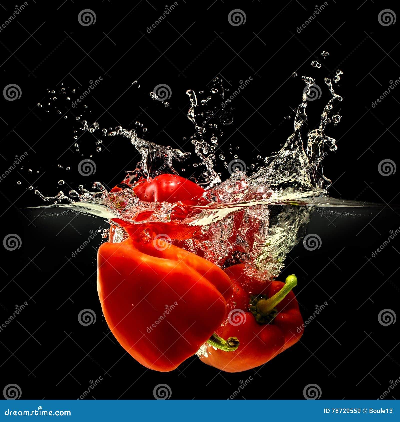 Grupp av spansk peppar som faller i vatten på svart