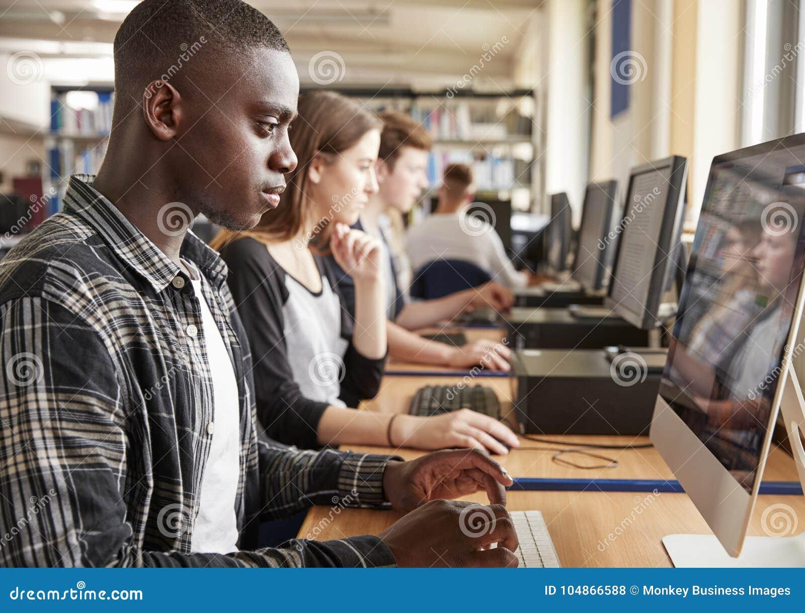 Grupp av studenter som använder datorer i högskolaarkiv