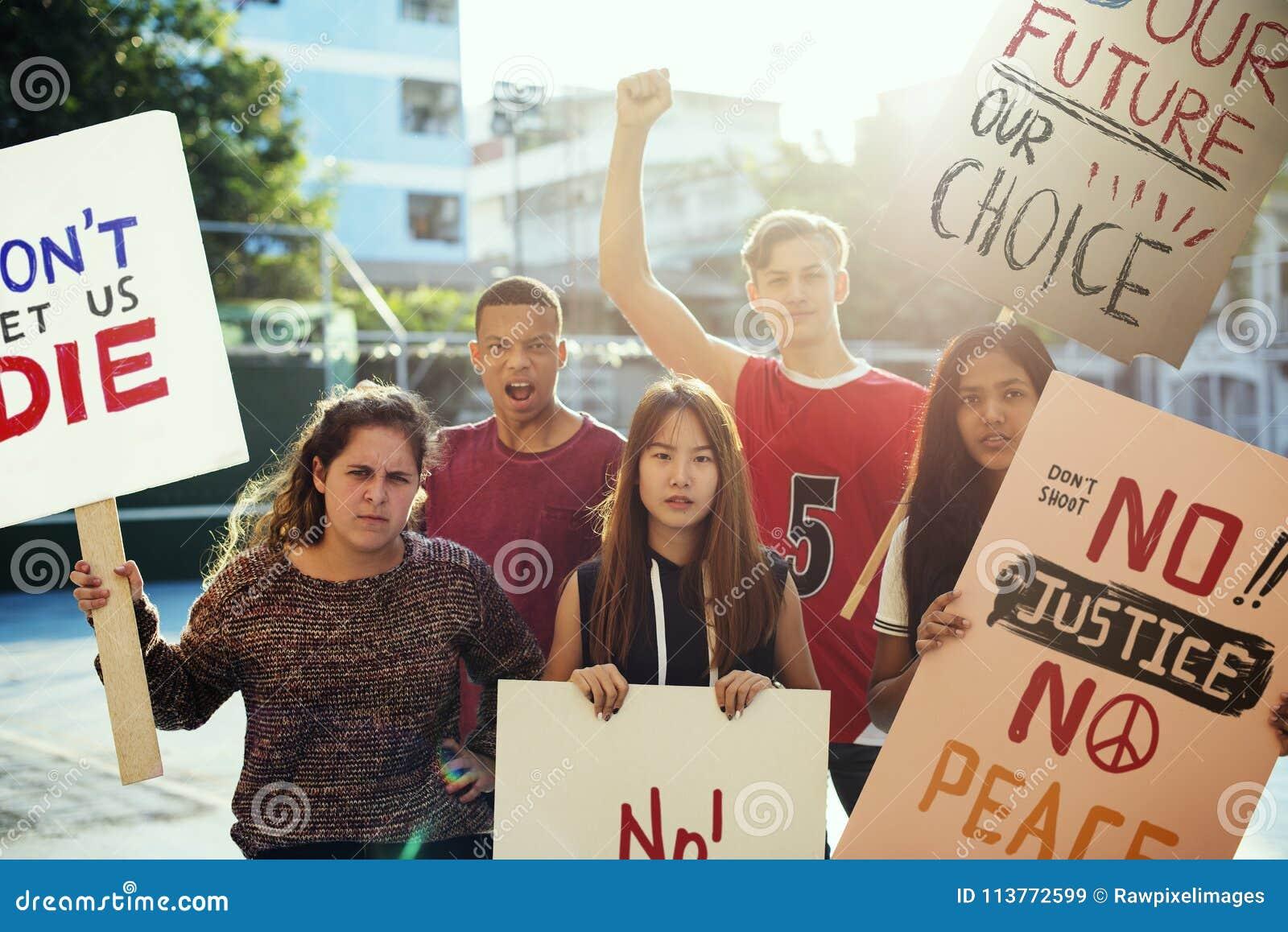 Grupp av tonåringar som protesterar begrepp för fred för rättvisa för hållande affischer för demonstration antiwar