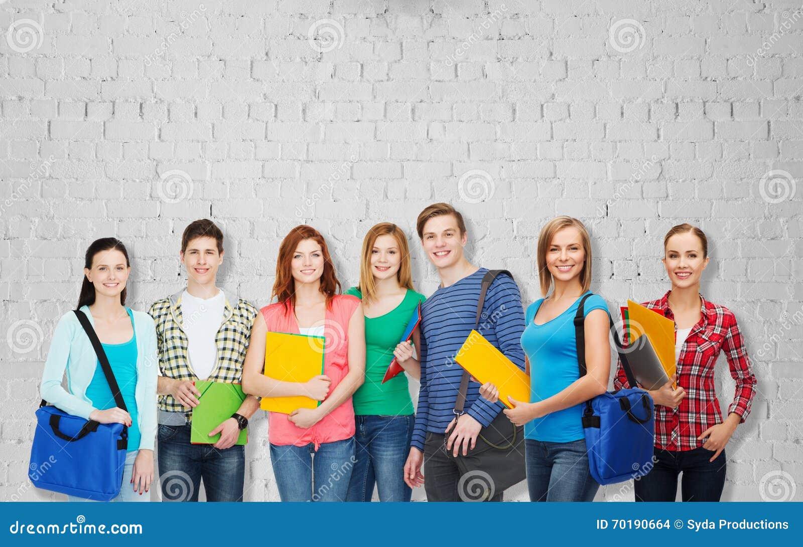 Grupp av tonårs- studenter med mappar och påsar