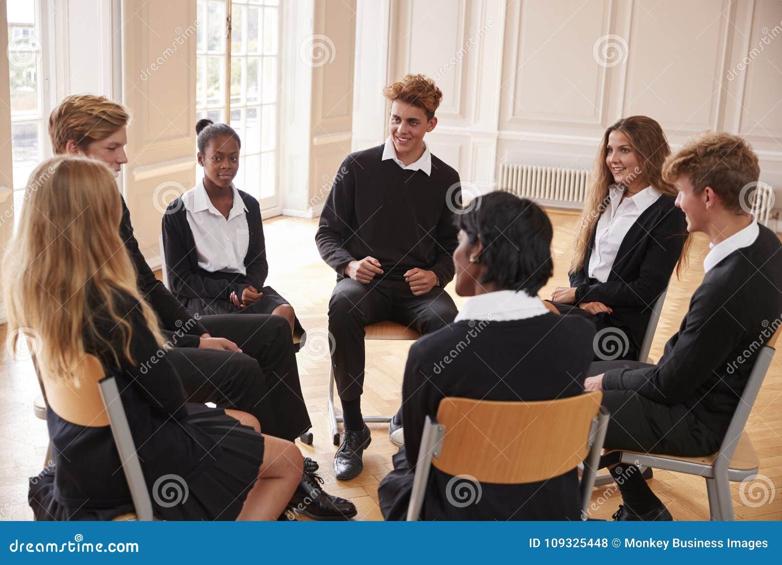Grupp av tonårs- studenter som har diskussion i grupp tillsammans