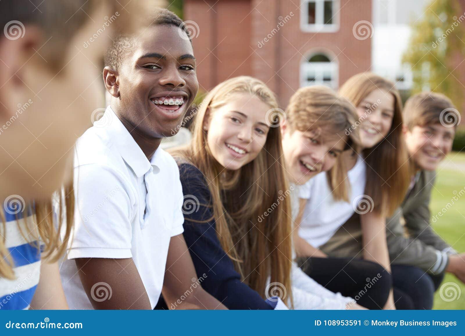 Grupp av tonårs- studenter som sitter utanför skolabyggnader