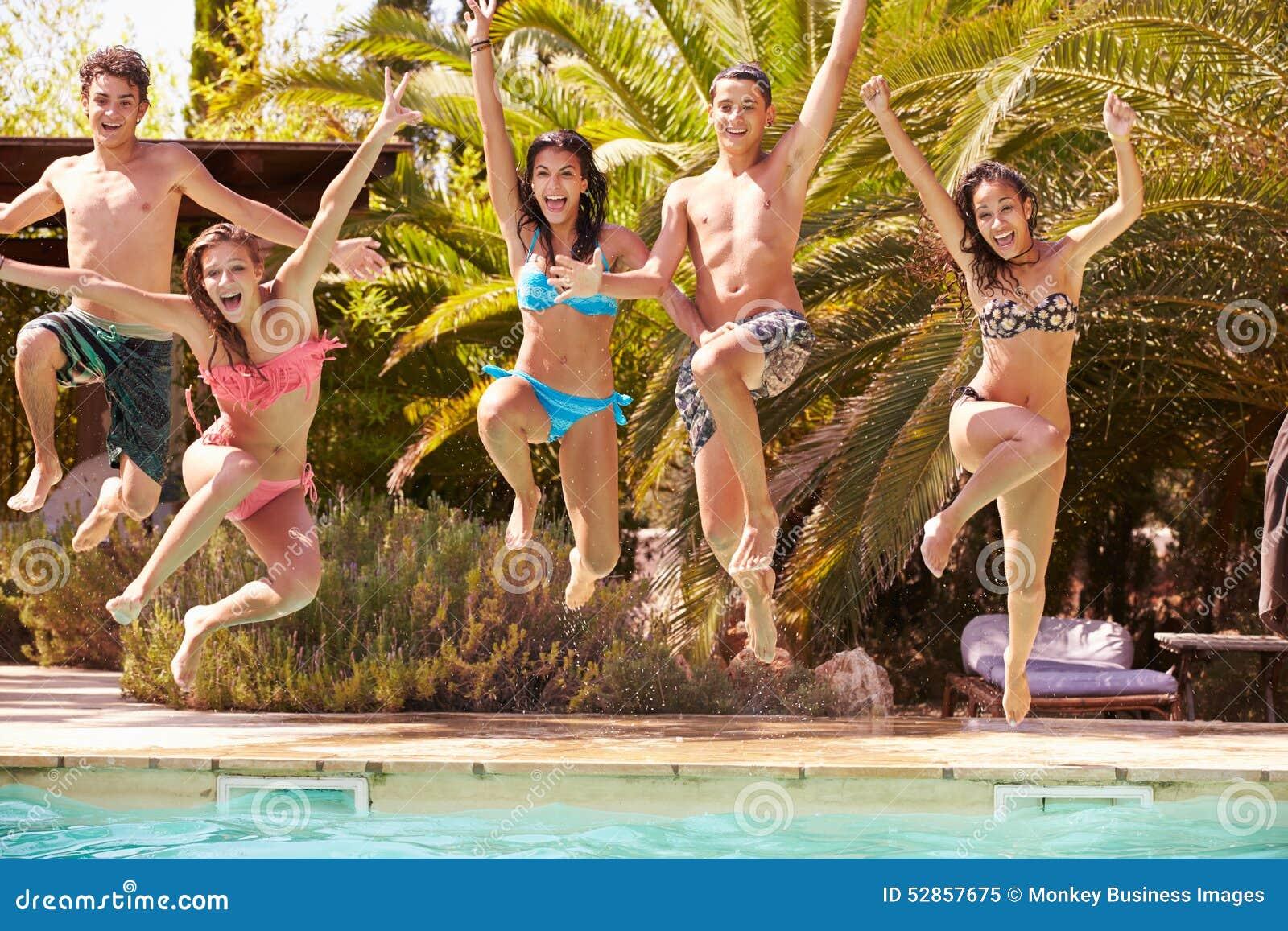 Grupp av tonårs- vänner som hoppar in i simbassäng