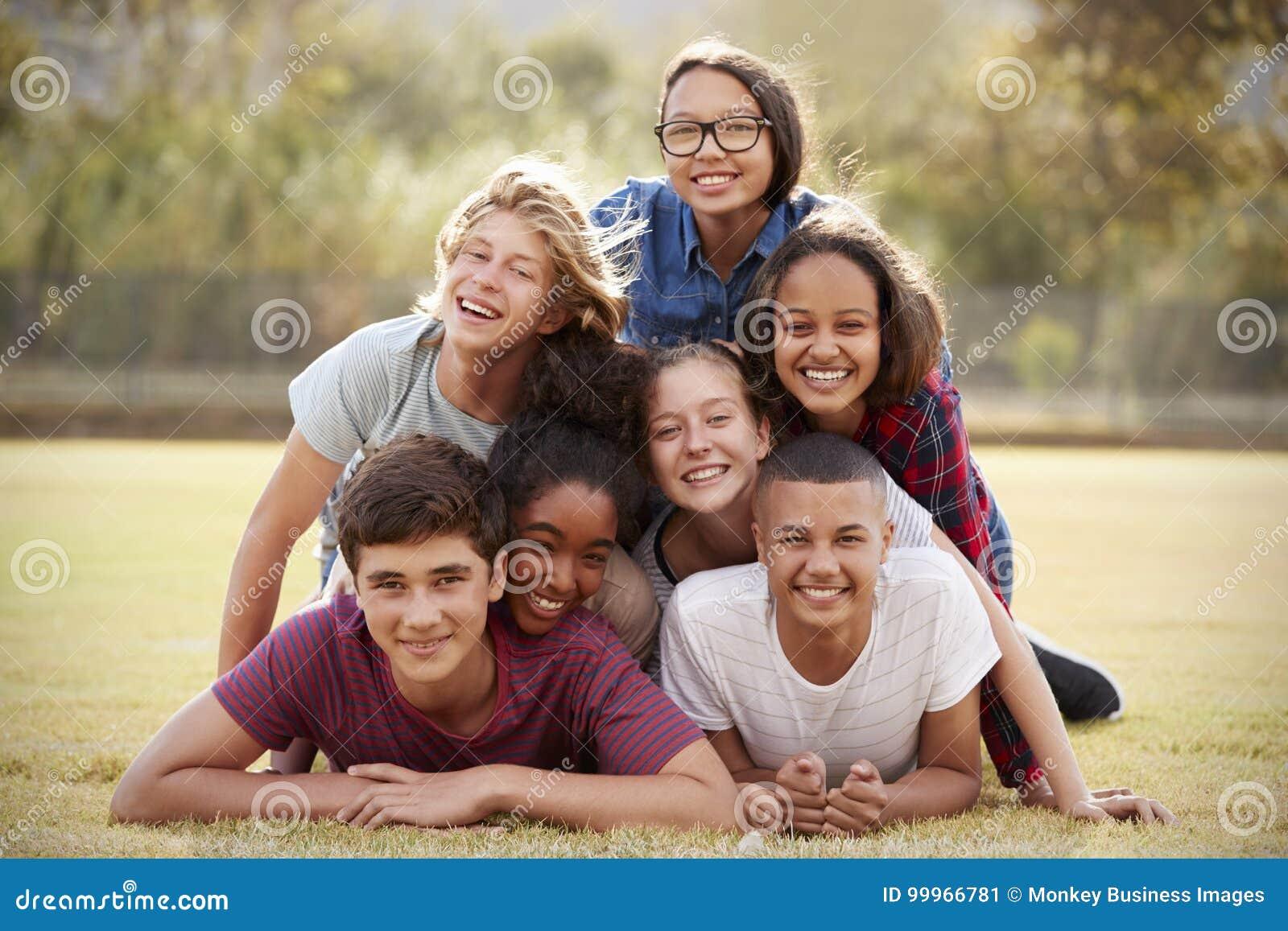 Grupp av tonårs- vänner som ligger i en hög på gräs