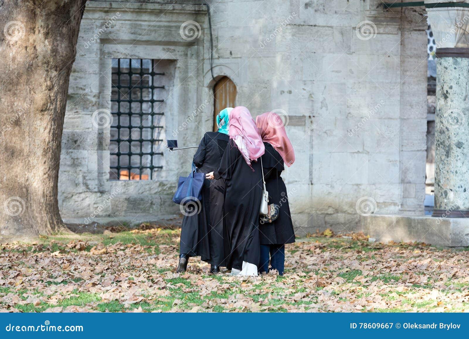 Grupp av tre islamiska klädda damer som gör självståendefotoet