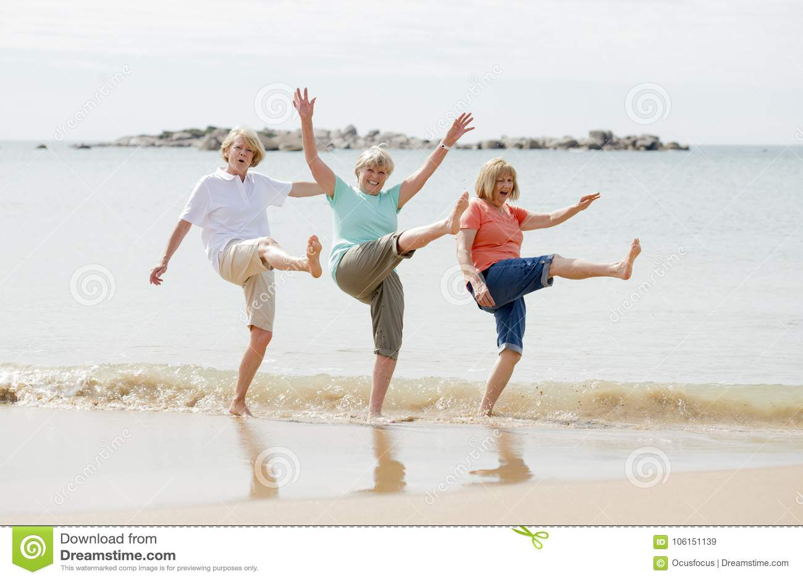 Grupp av tre mogna pensionerade kvinnor för pensionär på deras 60-tal som har gyckel som tillsammans tycker om lyckligt gå på le