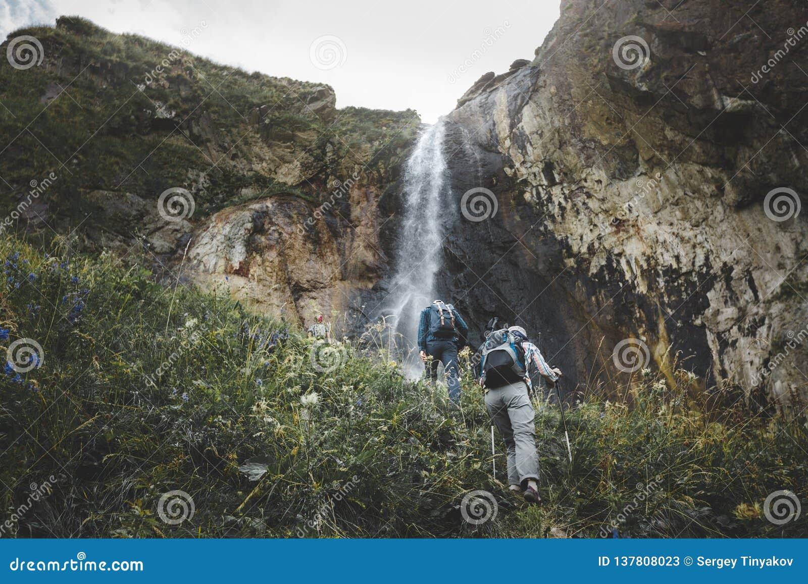 Grupp av turister som går som är stigande till vattenfallet Utomhus- begrepp för loppaffärsföretag