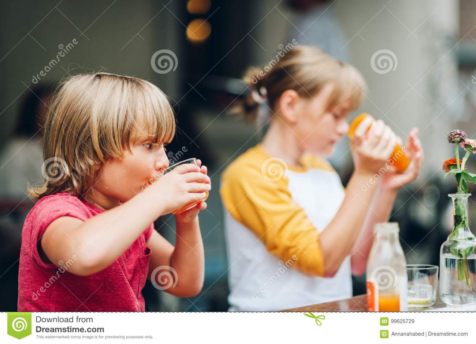 Grupp av två roliga ungar som har drinken i kafé
