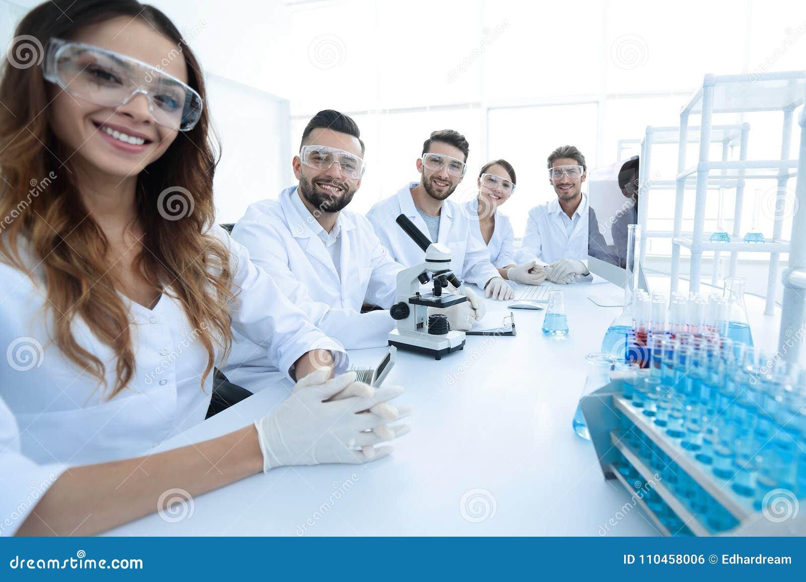 Grupp av ung cliniciansexperimenterande i forskningslaboratorium