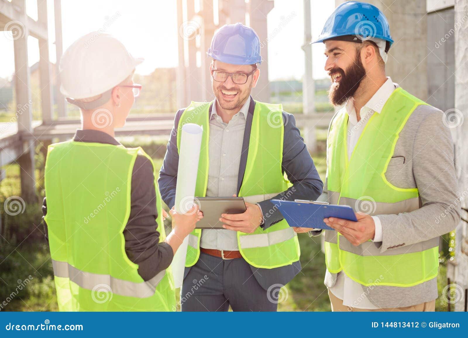 Grupp av unga arkitekter eller affärspartners som möter på en konstruktionsplats