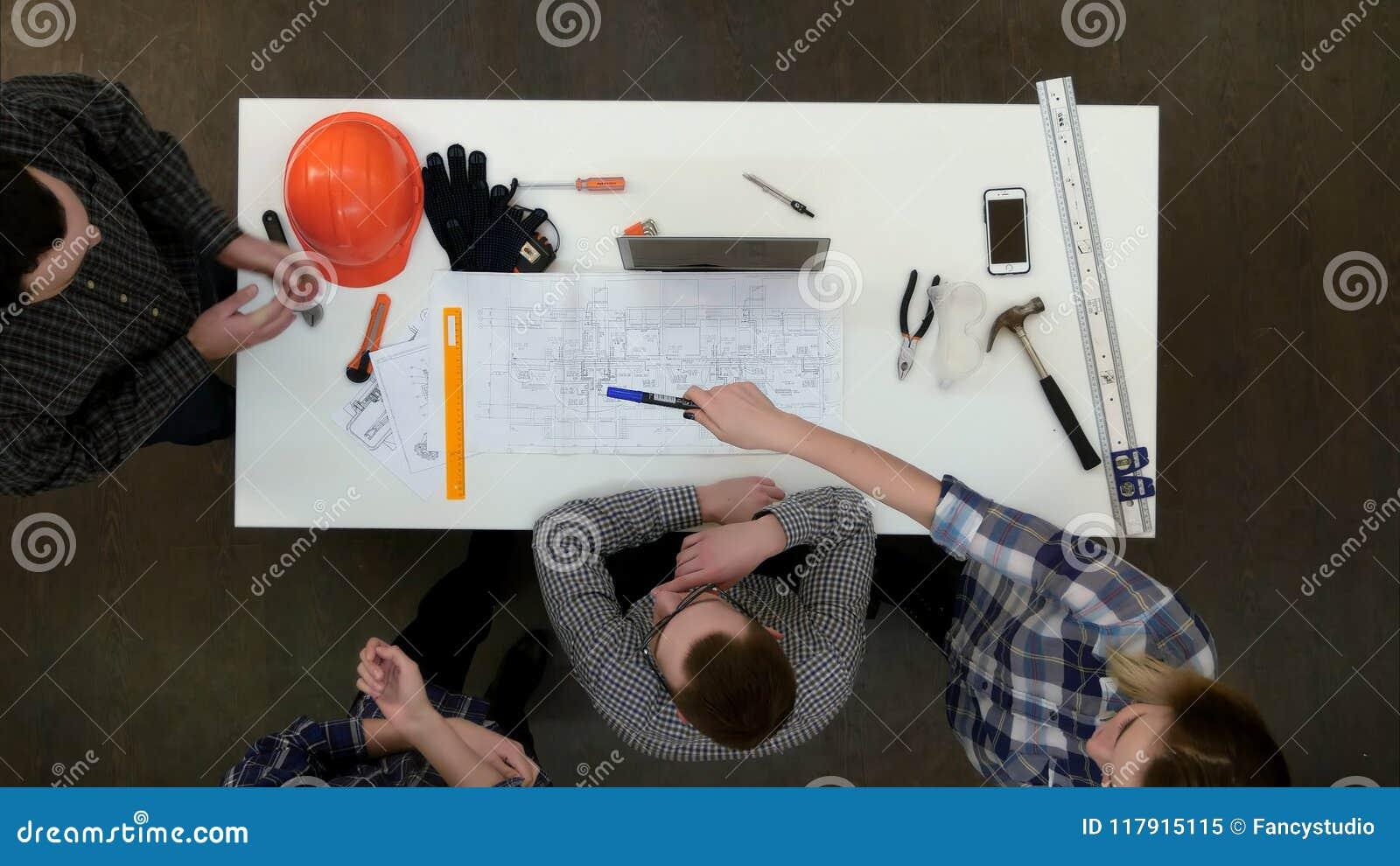 Grupp av unga arkitekter som arbetar på teckningar och gör mätningar med linjalen och avdelaren