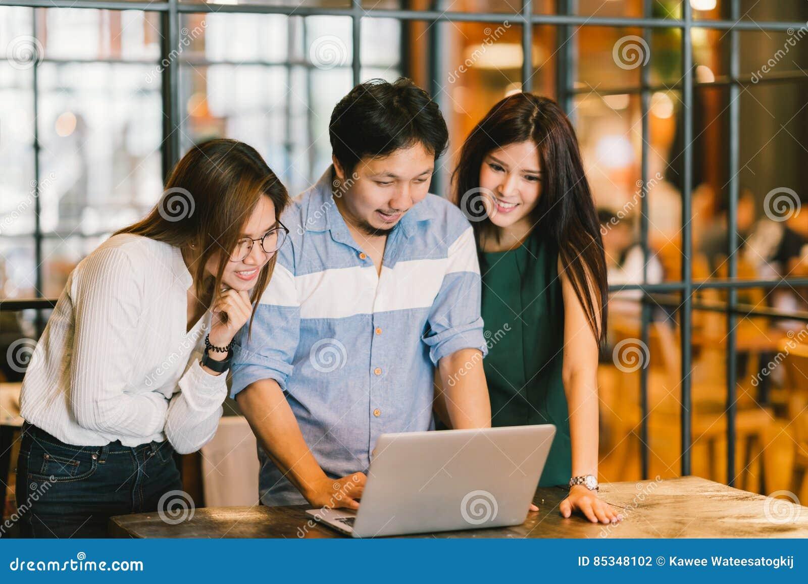Grupp av unga asiatiska affärskollegor i tillfällig diskussion för lag, startup affärsmöte eller teamworkkläckning av ideerbegrep