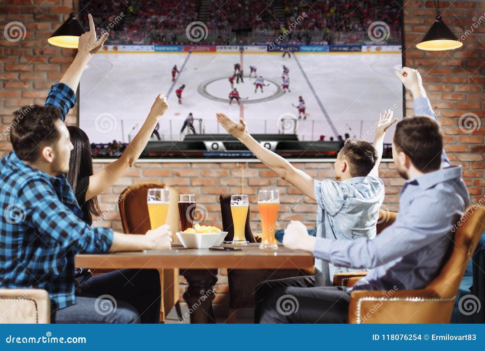 Grupp av unga härliga vänner som håller ögonen på TV och hurrar för deras lag, medan vila i bar