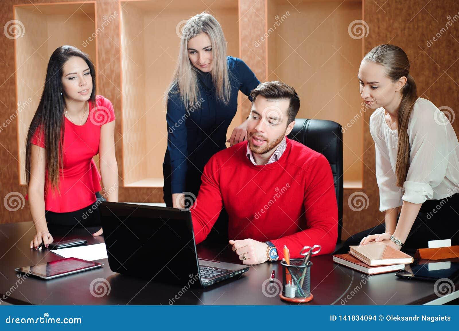 Grupp av unga kollegor som använder bärbara datorn på kontoret