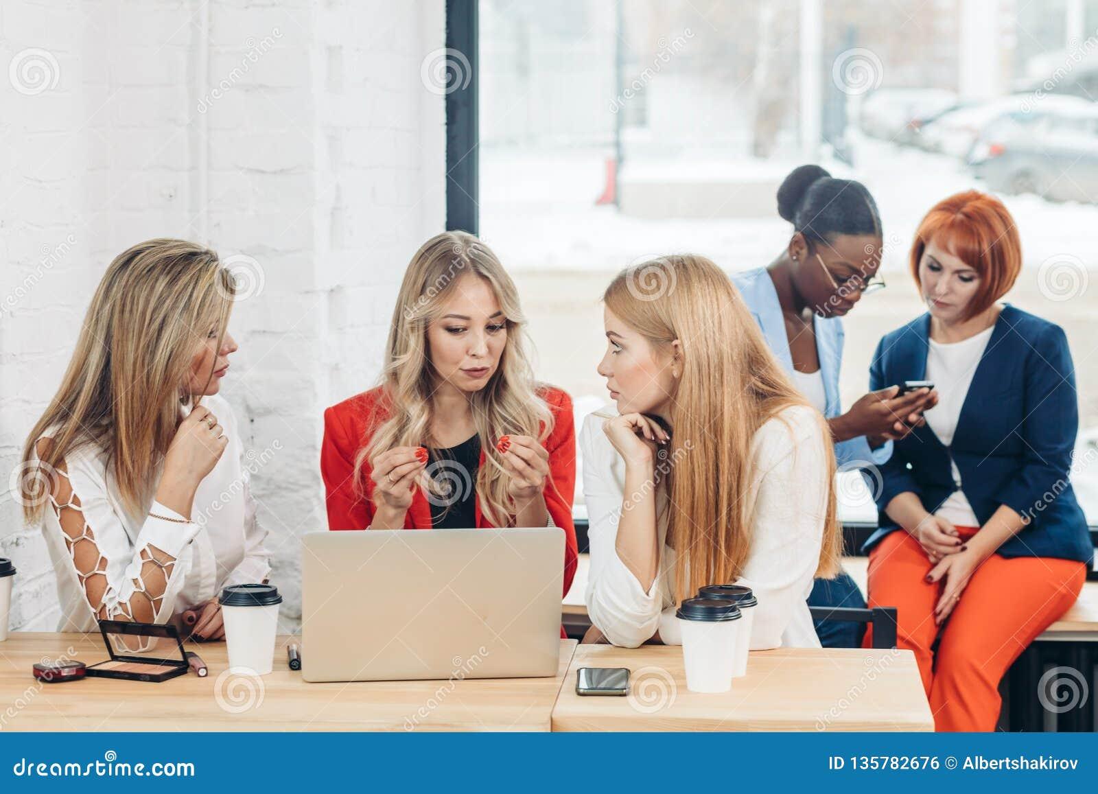 Grupp av unga kvinnor som diskuterar idérikt projekt under arbetsprocess