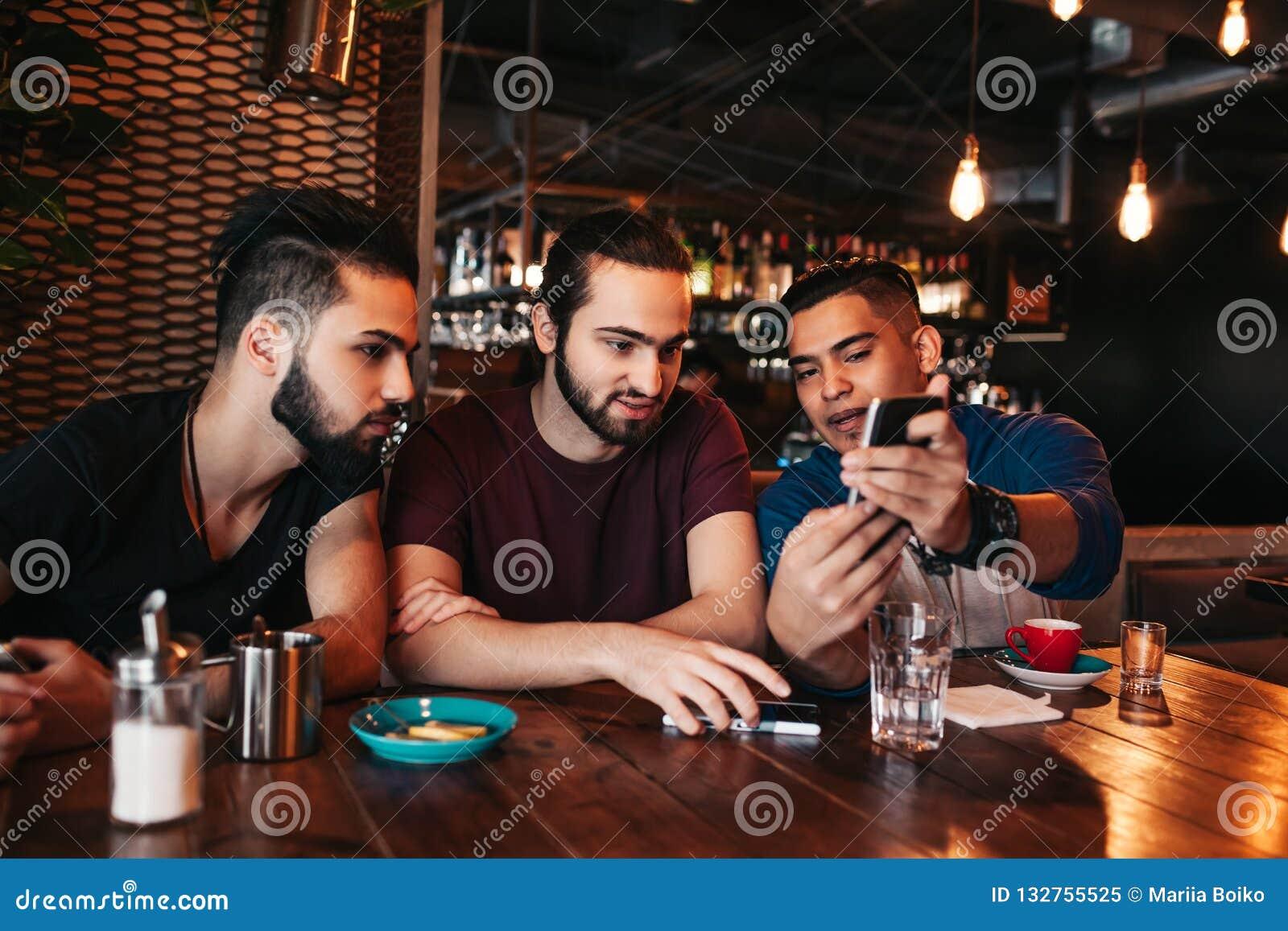 Grupp av unga män för blandat lopp som talar och använder telefonen i vardagsrumstång Blandras- vänner som har gyckel i kafé