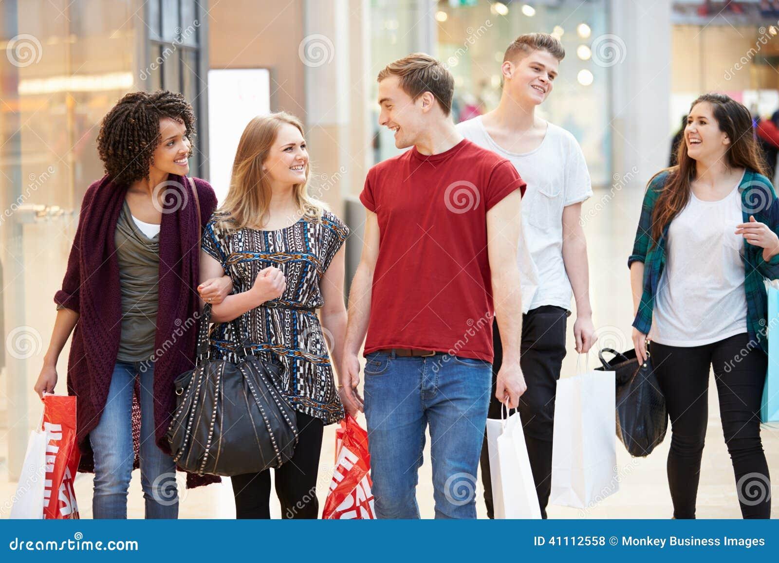 Grupp av unga vänner som tillsammans shoppar i galleria