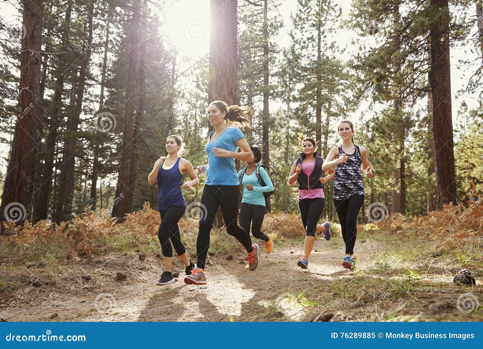 Grupp av unga vuxna kvinnor som kör i en skog, slut upp