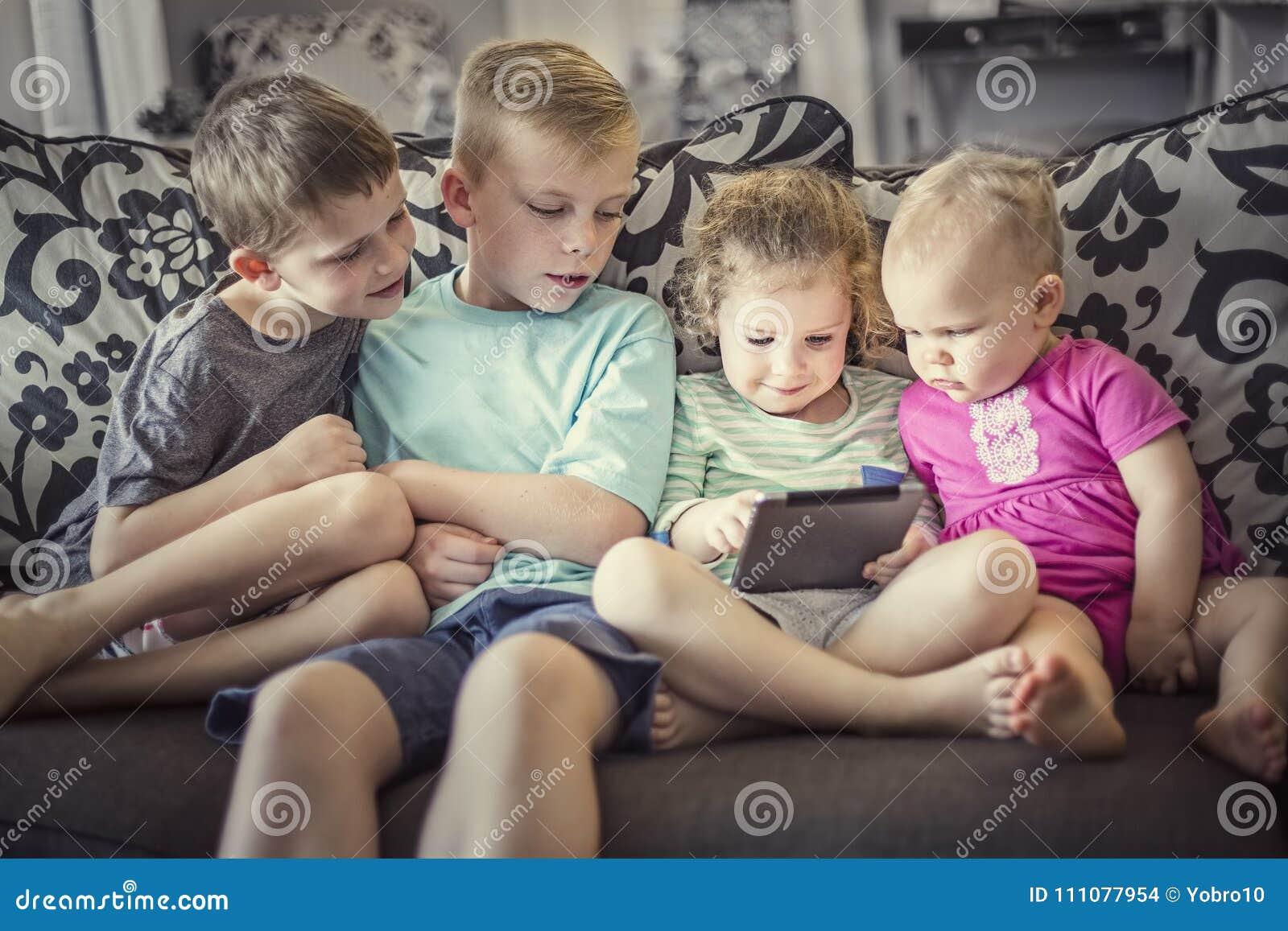 Grupp av ungar som spelar med elektroniska apparater för en minnestavla