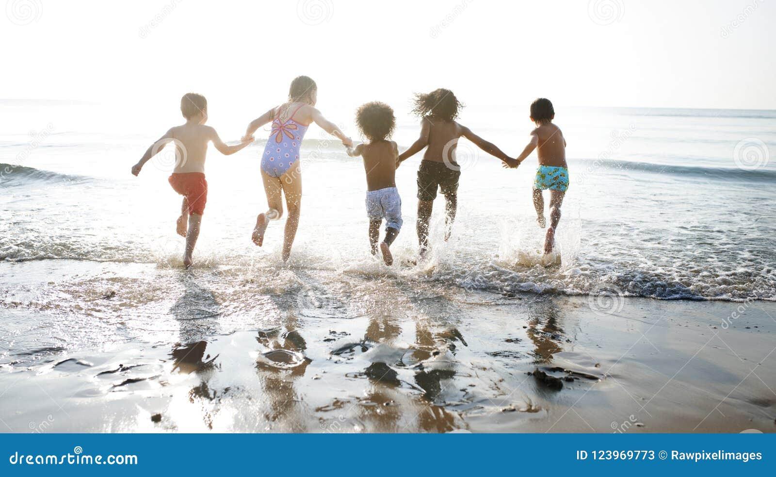 Grupp av ungar som tycker om deras tid på stranden