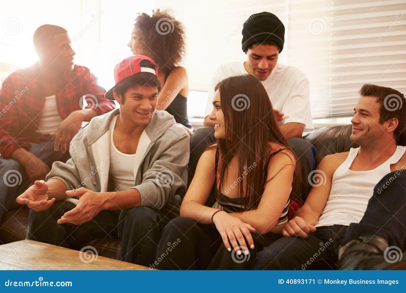 Grupp av ungdomarsom sitter på Sofa And Talking
