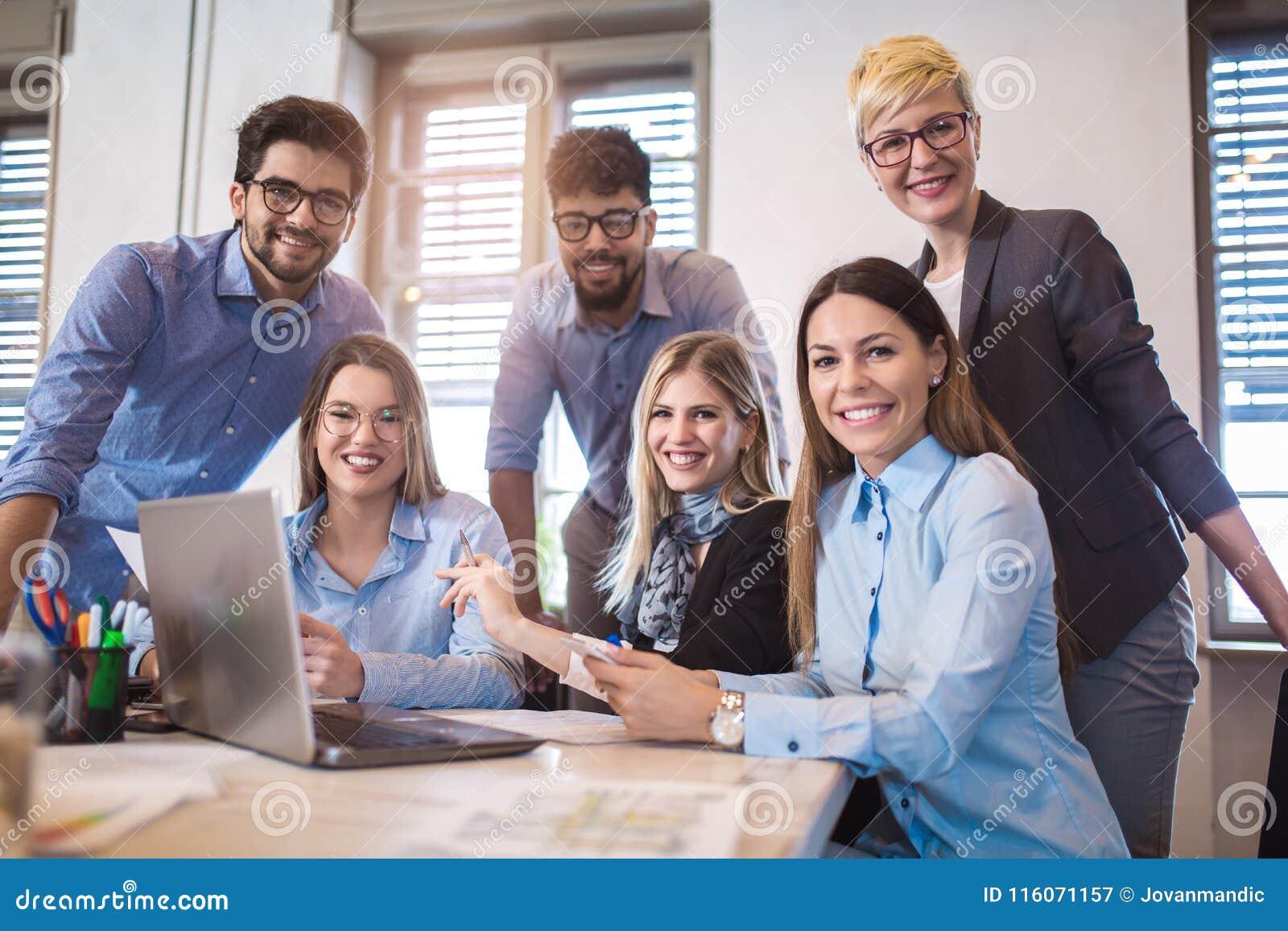 Grupp av ungt affärsfolk i smarta tillfälliga kläder som tillsammans arbetar