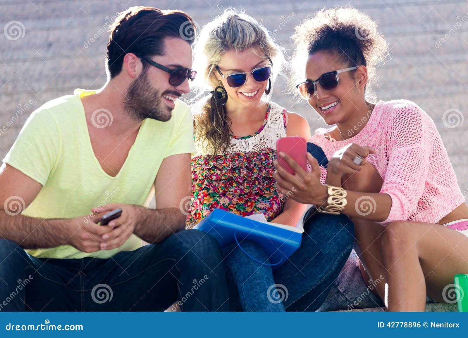 Grupp av universitetsstudenter som använder mobiltelefonen i gatan