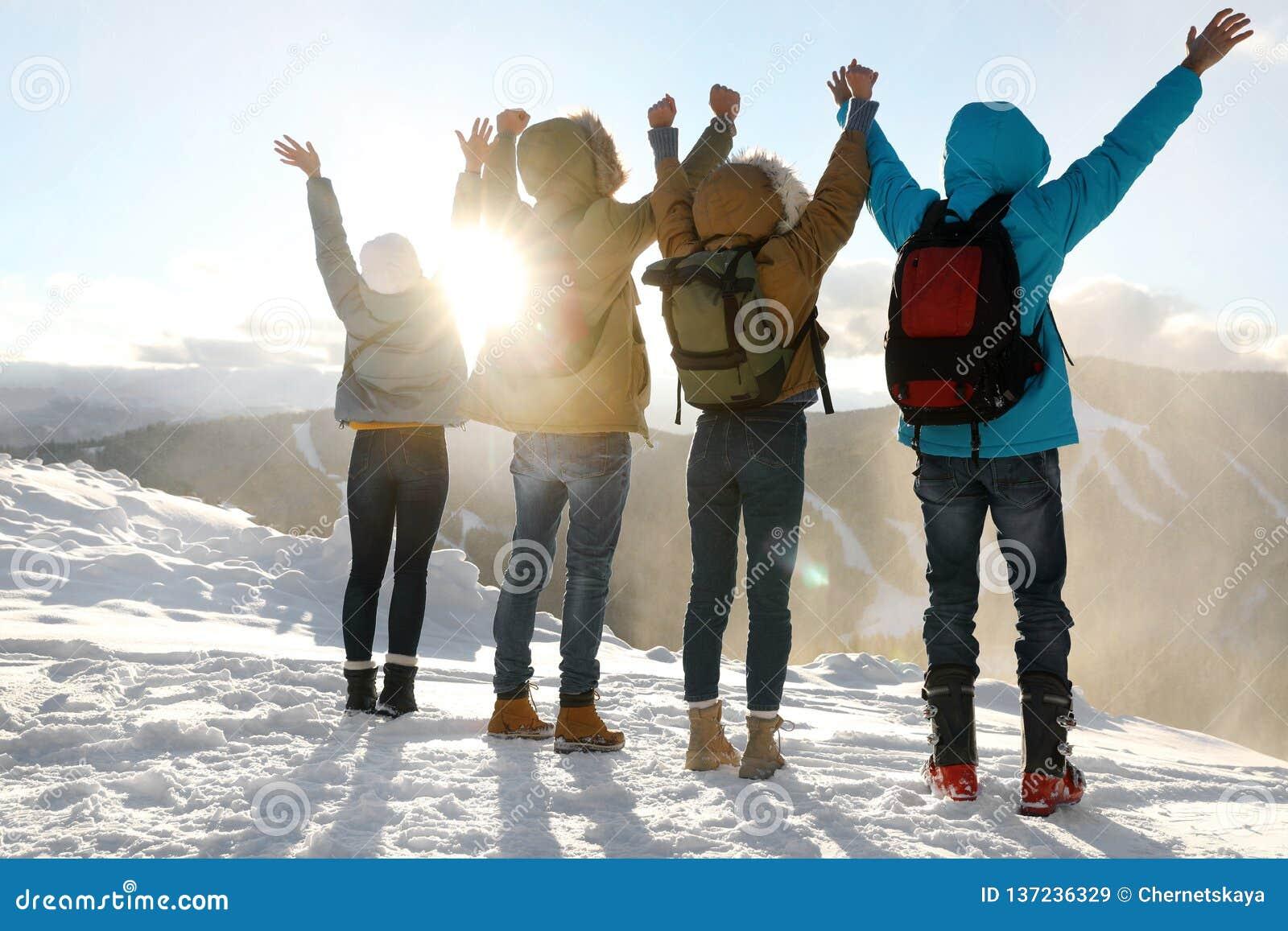 Grupp av upphetsade vänner med ryggsäckar som tycker om sikt under vintersemester