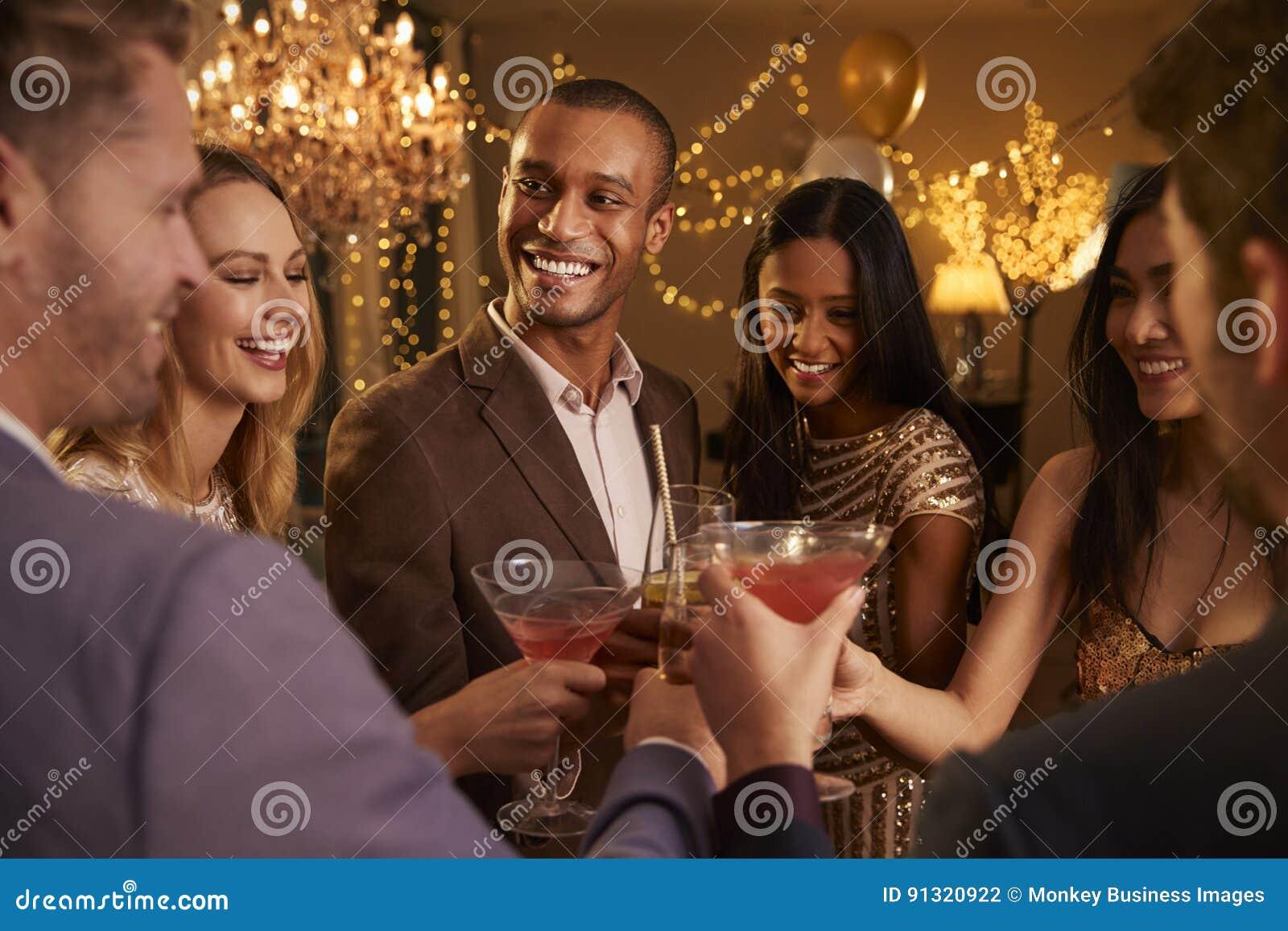 Grupp av vänner med drinkar som tycker om cocktailpartyet