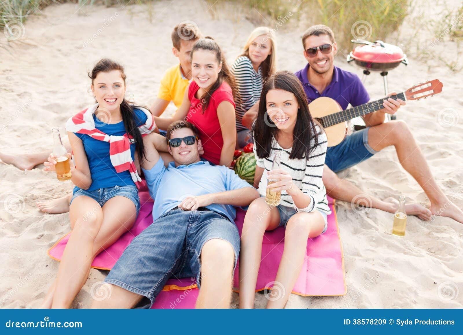 Grupp av vänner med gitarren som har gyckel på stranden