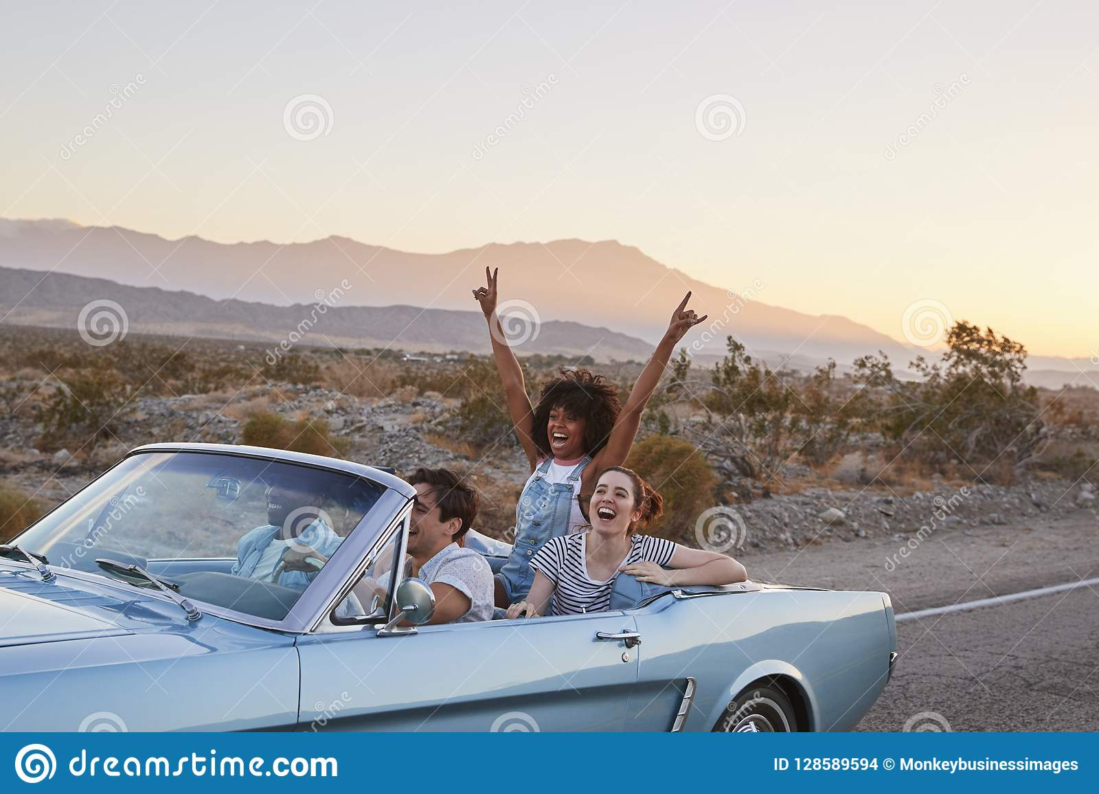 Grupp av vänner på vägturen som kör den klassiska konvertibla bilen