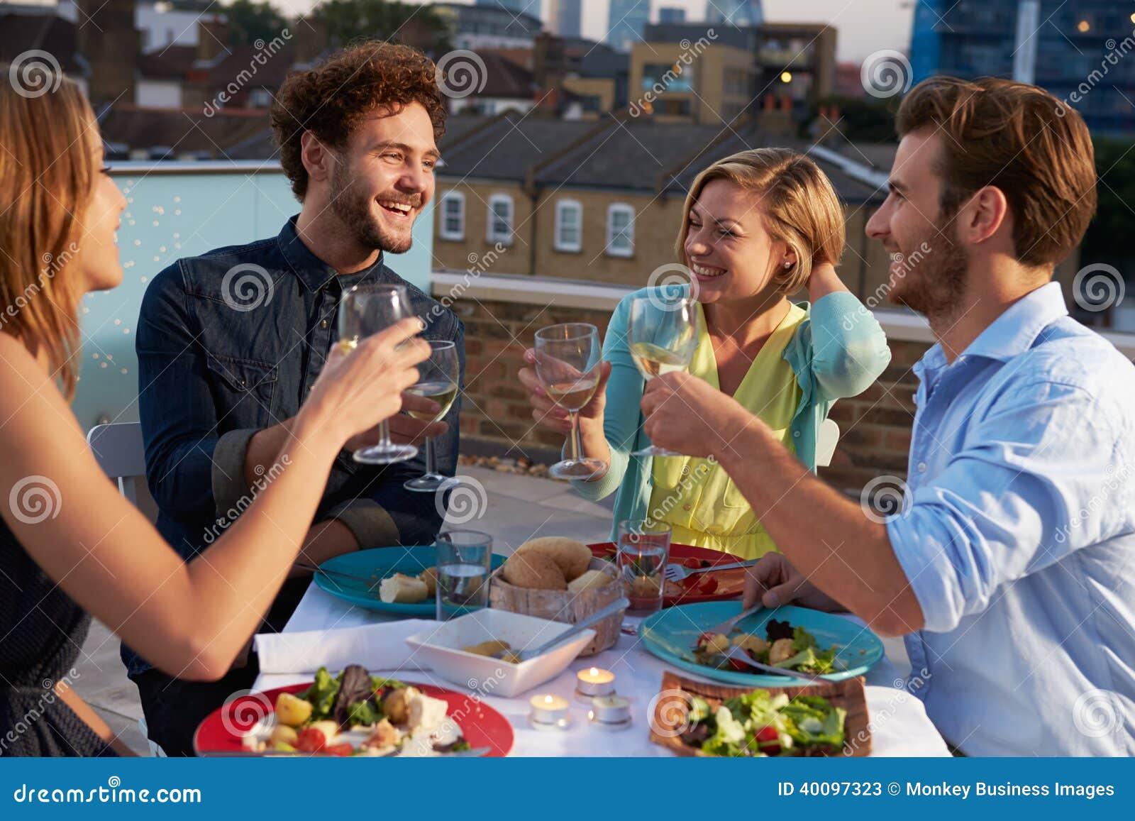 Grupp av vänner som äter mål på takterrass