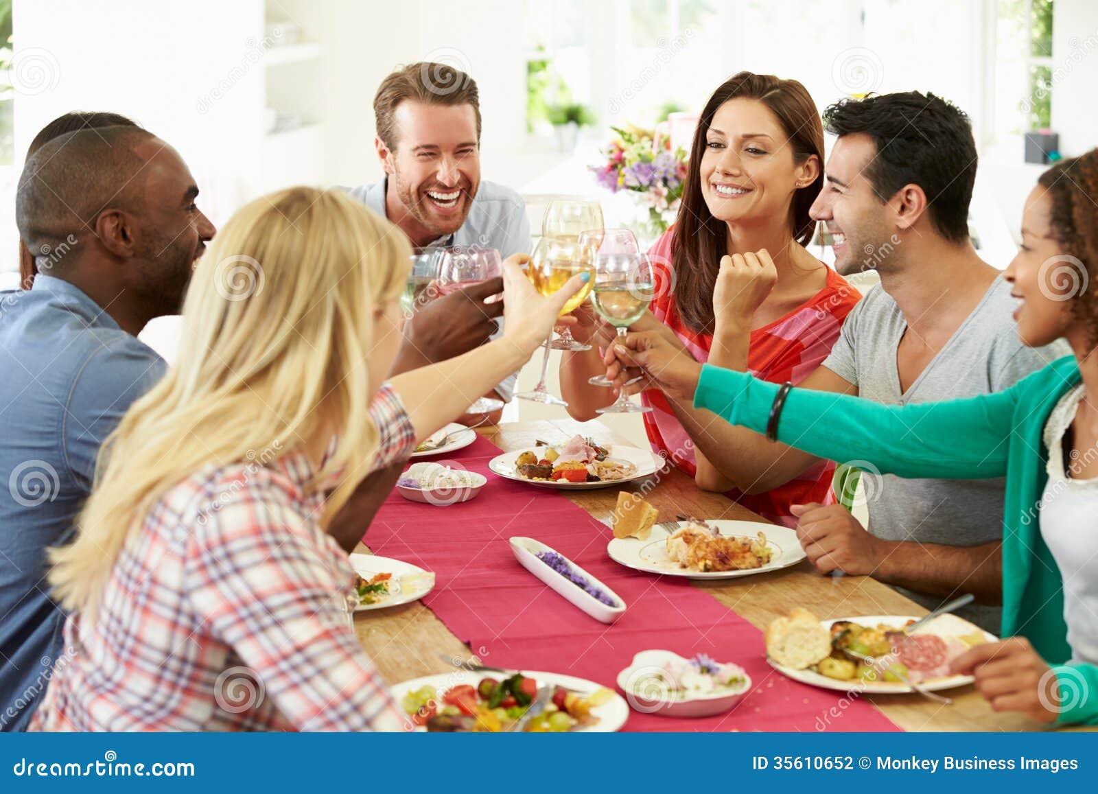 Grupp av vänner som gör rostat bröd runt om tabellen på matställepartiet