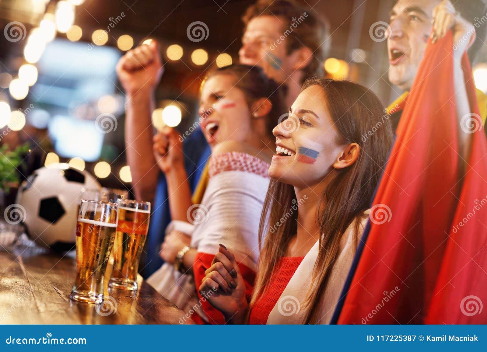 Grupp av vänner som håller ögonen på fotboll i bar