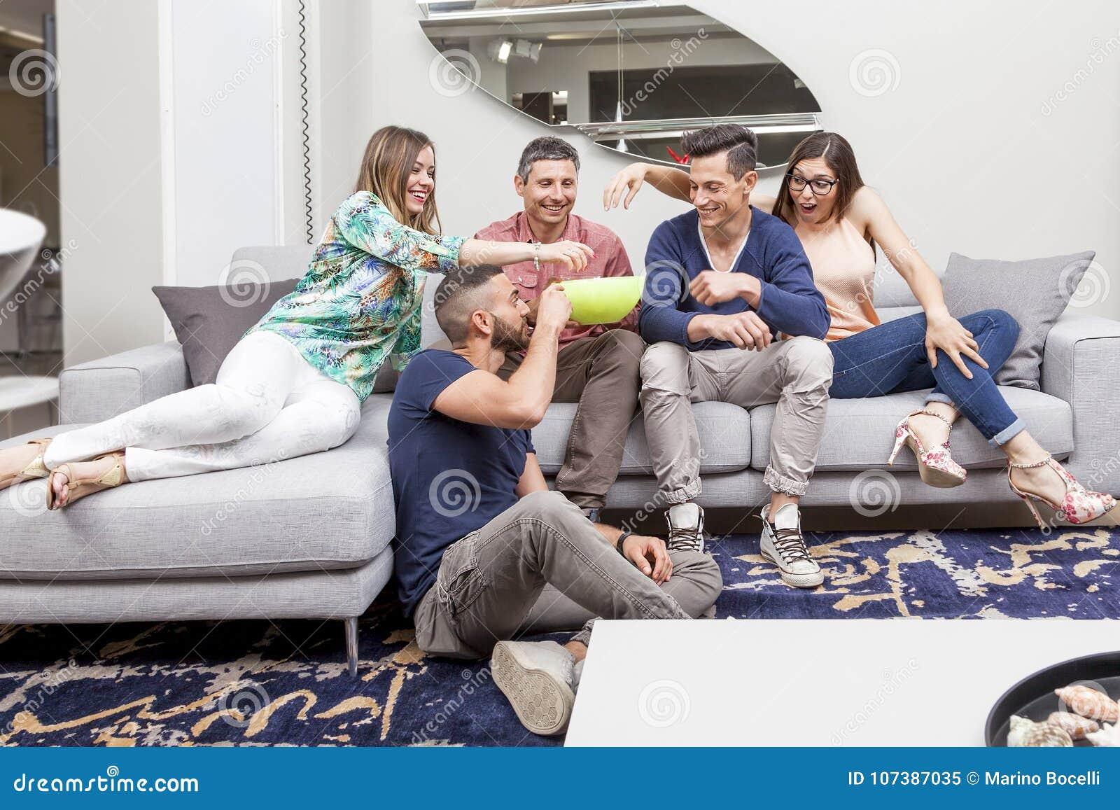 Grupp av vänner som håller ögonen på tv och äter popcorn på soffan