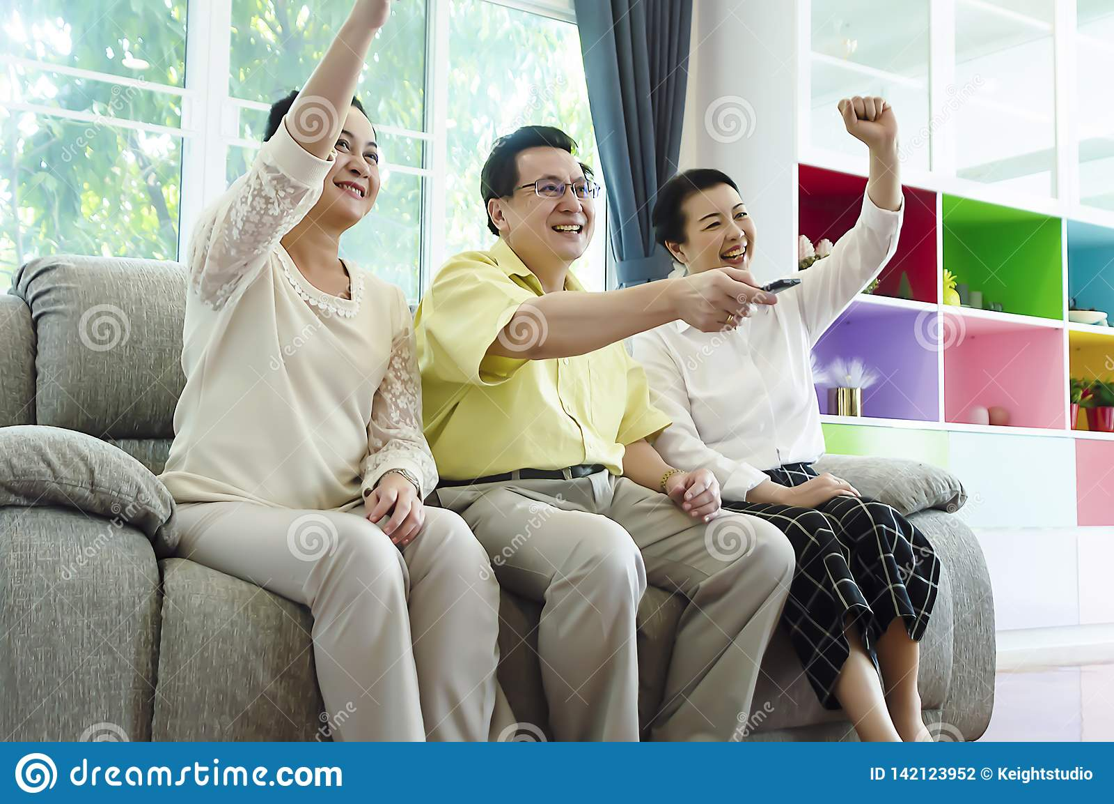 Grupp av vänner som håller ögonen på tv sitta tillsammans hemma på den bekväma soffan