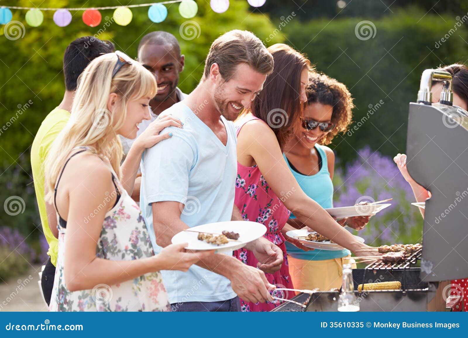 Grupp av vänner som har den utomhus- grillfesten hemma
