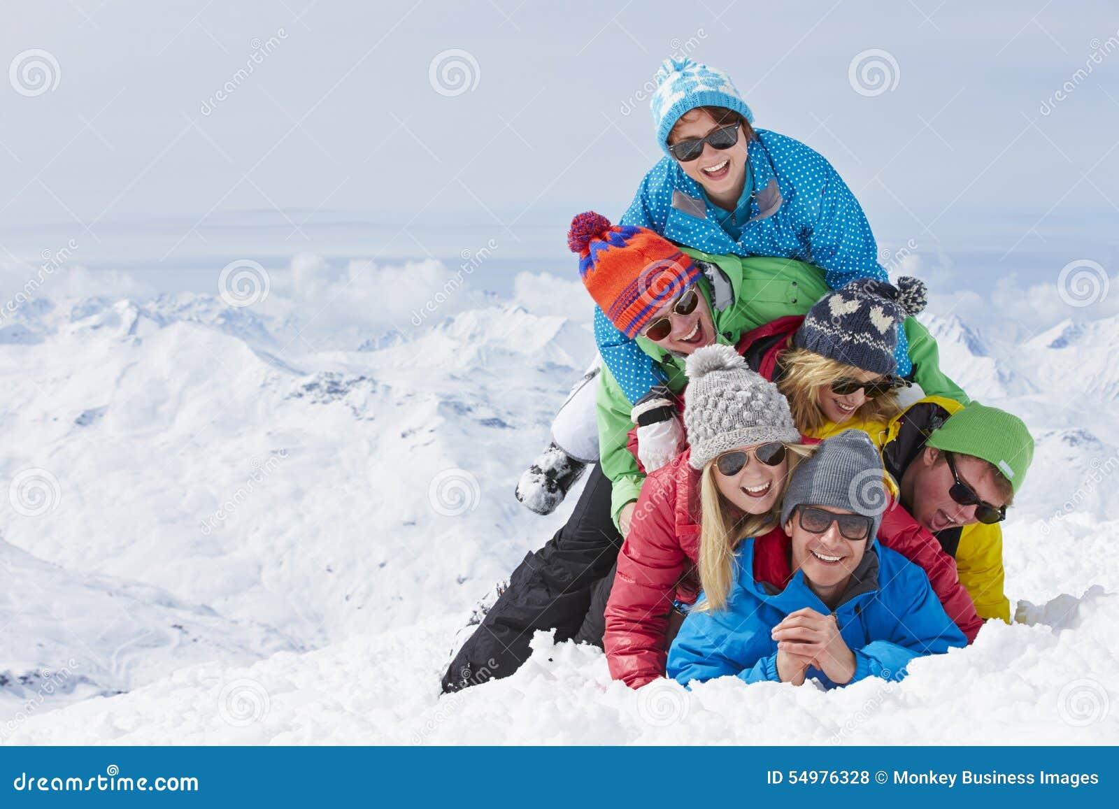 Grupp av vänner som har gyckel på Ski Holiday In Mountains