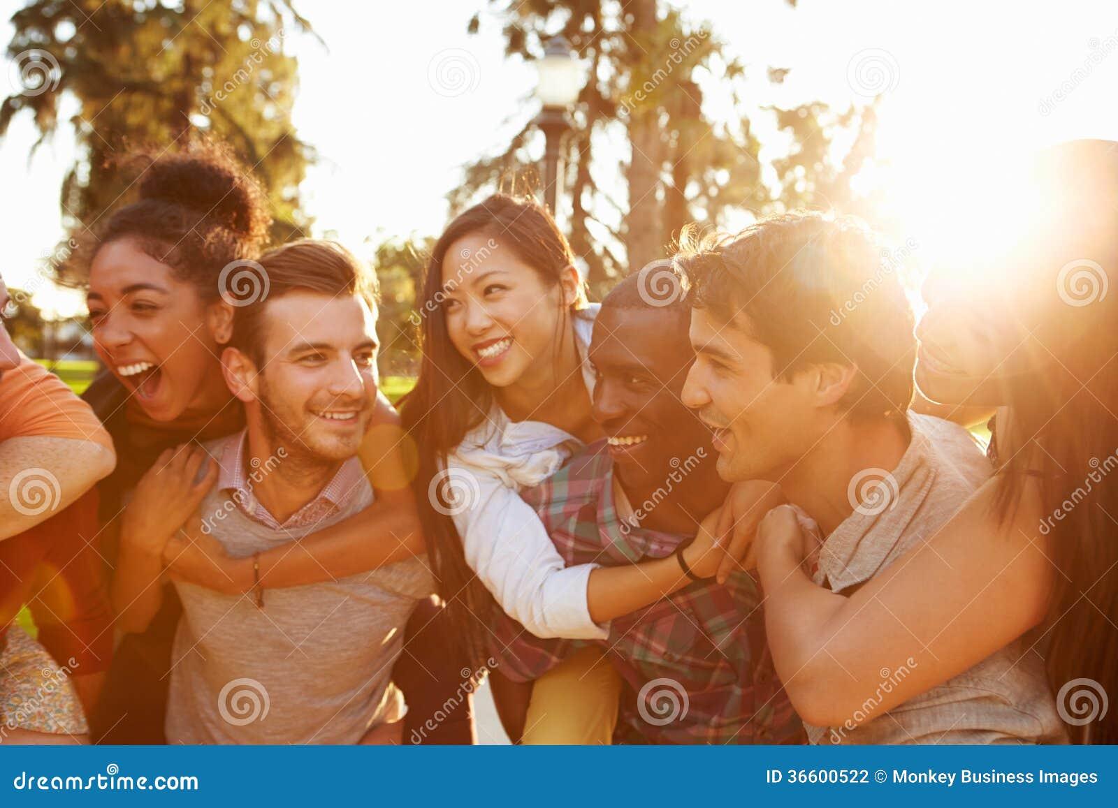 Grupp av vänner som har gyckel tillsammans utomhus