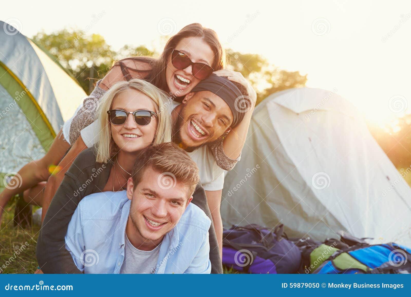 Grupp av vänner som har gyckel utanför tält på campa ferie