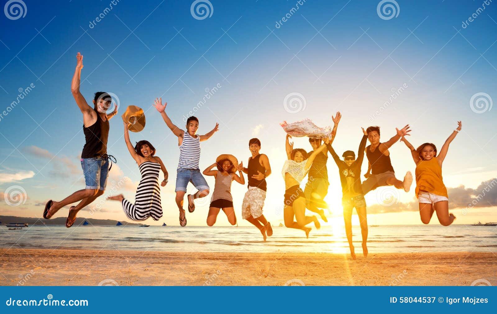 Grupp av vänner som hoppar på stranden