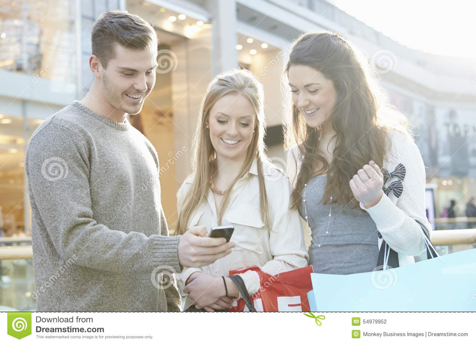 Grupp av vänner som shoppar i gallerian som ser mobiltelefonen
